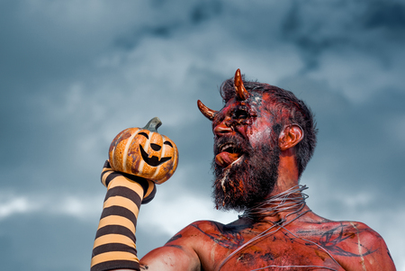 Halloween dragon with jack o lantern. Devil man holding pumpkin in striped sock. Satan with red tongue, beard, blood, wounds on face. Demon with bloody horns on head. Evil, horror, hell concept.
