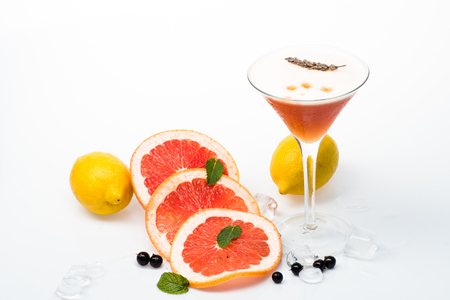Drink and food. Cocktail isolated on white background. Alcoholic beverage and fruit at restaurant. Fruit slice and cocktail glass at bar. Party and summer vacation.