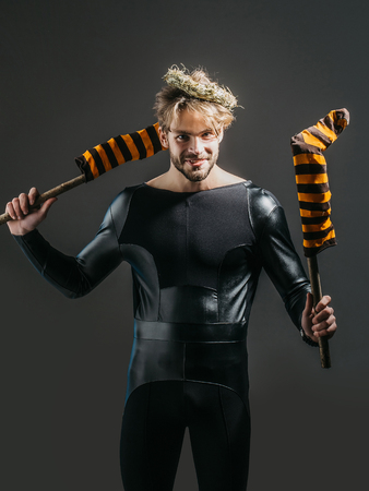Halloween man smiling in black costume on dark background. Happy macho holding striped stockings on sticks. Holiday celebration concept. Trick or treat