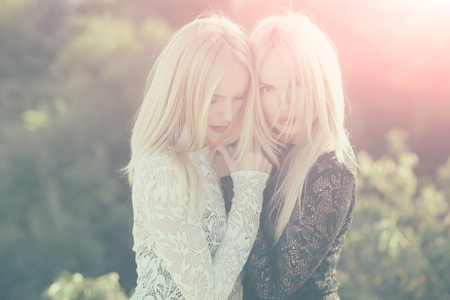 Contrasts and opposites concept. Sisters twins posing on sunny natural landscape. Dualism and dualistic nature. Two women with red lips and long blond hair. Beauty and fashion. Фото со стока
