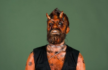 Halloween demon with red blood eyes, beard, wounds on face. Man devil on grey background. Evil, horror, hell, death concept. Satan with bloody horns on head. Holiday celebration, cosplay.