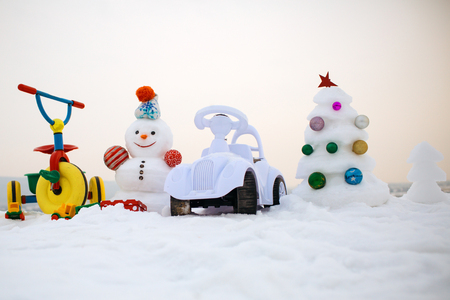 Snowman and snow xmas tree on white sky. Tricycle and toy car on snowy background. Christmas and new year. Festive surprise and presents. Winter holidays celebration concept.