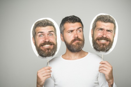 Guy or bearded man on grey background. Feeling and emotions. Hipster with serious, happy and scary face hold portrait nameplate. Barber fashion and beauty. Man with long beard and mustache.