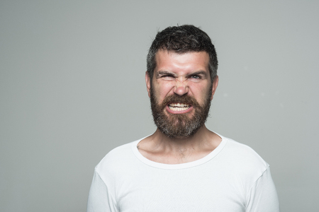 Hipster with angry face. Feeling and emotions. Guy or bearded man on grey background. Barber fashion and beauty. Man with long beard and mustache, copy space