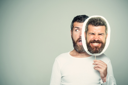 Man with long beard and mustache. Hipster with surprised and angry face hold portrait nameplate. Guy or bearded man on grey background. Feeling and emotions. Barber fashion and beauty., copy space Banco de Imagens