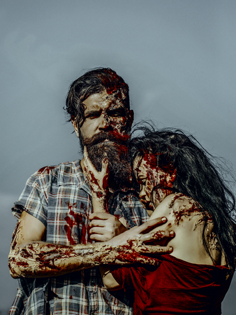 Halloween zombie couple hugging on blue sky. Vampire man with beard and wounds. Woman with red blood and brunette hair. War soldier and girl with bloody skin. Holiday celebration concept.