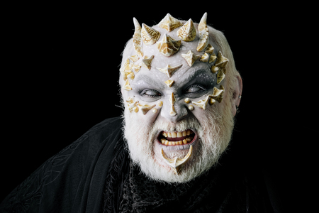 Evil face with dragon skin and grey beard. Man angry with blind eyes. Demon baring teeth on black background. Monster with thorns and horns. Horror and fantasy concept.