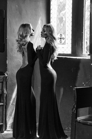 Two young women beautiful sensual blonde twin sisters in glamour long green dresses with sexy bare back standing opposite each other holding by hands