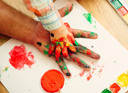 Fathers day and family. Hands in colorful paints and multicolor palette on white paper. Care, love or adoption concept. Arts and handprint painting. Support and protection. Stock Photo