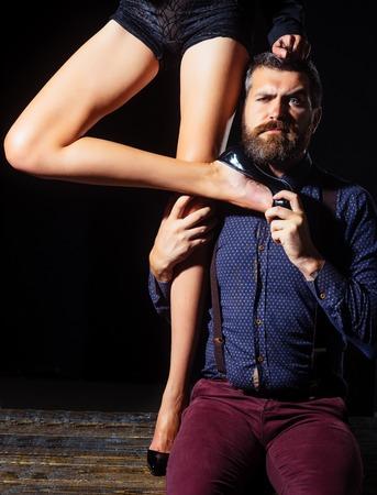 Romantiek en verliefd. Liefde en relaties, domineren. Benen van vrouw in schoenen bij de mens met baard. Mens in overhemd op zwarte achtergrond, matriarchie wordt geïsoleerd die. Jongen aan tafel met vrouwelijke benen. Stockfoto