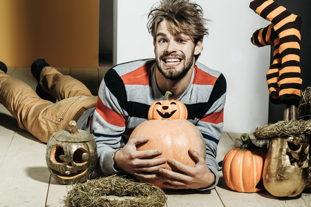 Halloween pumpkins, striped stockings and wreath. Man with messy hair happy smiling on floor. Autumn and harvest season. Holidays celebration concept. Trick or treat.