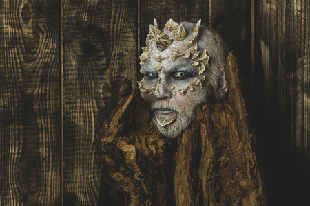 druid: Goblin with horns on head. Monster with sharp thorns and warts. Man with dragon skin and bearded face. Druid behind old bark on wooden wall. Tree spirit and fantasy concept. Stock Photo