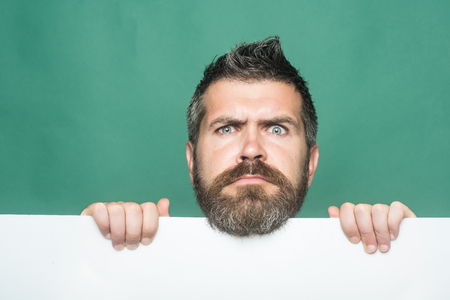 Man with long beard and mustache. Barber fashion and beauty marketing. Guy or bearded man on green background. Hipster with serious face hold paper. Feeling and emotions.