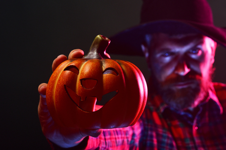 Halloween jack o lantern and blurred man. Mystery and magic concept. Autumn holiday celebration. Pumpkin in hand of hipster in wizard hat on dark background. Trick or treat. Stock Photo