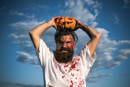 symbol victim: Halloween hipster grinding teeth with anger. Man holding pumpkin overhead on cloudy blue sky. Soldier in bloody torn tshirt with jack o lantern. Aggression, war concept. Autumn holiday celebration.