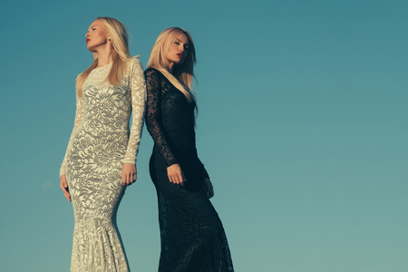 Opposites and contrasts concept. Women wearing black and white dresses. Fashion and beauty. Two girls with long blond hair posing on blue sky. Choice, decision and future, copy space Stok Fotoğraf - 87988819