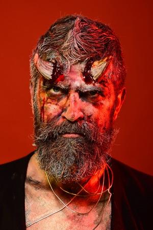 Halloween-demon met bloedige hoornen op hoofd. Mensenduivel op rode achtergrond. Hell, death, evil, horror concept. Satan met baard, bloed, wonden op het gezicht. Feestviering, cosplay.