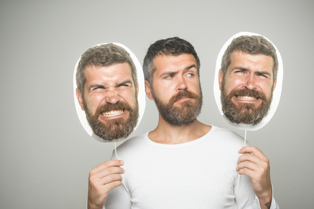 Feeling and emotions. Man with long beard and mustache. Barber fashion and beauty. Hipster with serious and angry face hold portrait nameplate. Guy or bearded man on grey background. Banco de Imagens