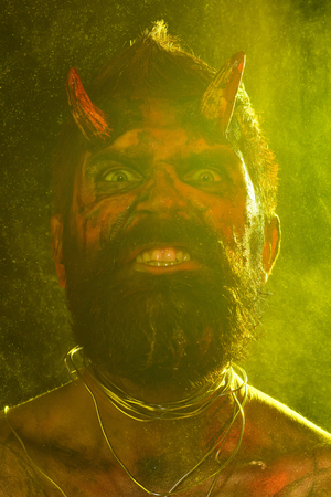 Halloween man demon with scary face in yellow light. Holiday celebration, cosplay. Satan with beard, red blood, wounds. Hell, death, evil, horror concept. Devil with bloody horns on head. Stock Photo