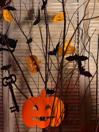 Halloween-Dekorationen aus Papier. Laternen Jacks O in der orange Farbe, die an den Baumasten hängt. Fledermäuse, Katzen und Kürbisse als Raumdekoration. Halloween traditionelles Dekorkonzept. Standard-Bild - 87989161