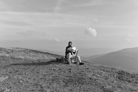 handsome bearded man with mustache long lush beard in checkered shirt black hat sit on stone and reading map with cup on mountain top on sunny day Stok Fotoğraf