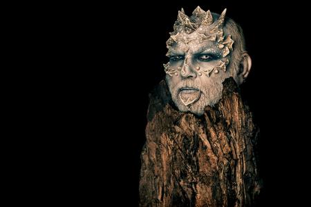 트리 정신 및 판타지 개념입니다. 날카로운 가시와 사마귀가있는 괴물. 블랙에 고립 된 오래 된 나무 껍질 뒤에 사제. 머리에 뿔 고블린입니다. 용 피부