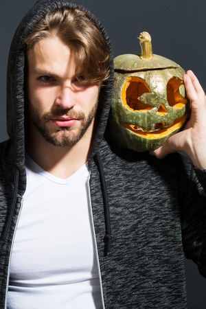 young handsome bearded sexy man with stylish hair in white shirt and jacket in studio on grey wall background holds orange golden halloween traditional pumpkin with scary face, copy space