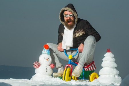 Excited hipster in pilot glasses and hood on bike. Man riding tricycle on grey sky. Holiday celebration concept. Christmas and new year fun. Snowman and snow xmas tree on winter landscape.