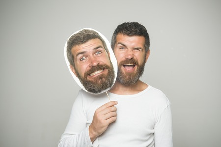 Guy or bearded man on grey background. Man with long beard and mustache. Barber fashion and beauty. Feeling and emotions. Hipster with happy face hold portrait nameplate.