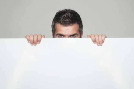 Feeling and emotions. Hipster hide face behind white paper. Man with stylish hair. Guy on grey background.