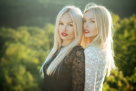 Two women with red lips and long blond hair. Dualism and dualistic nature. Contrasts and opposites concept. Beauty and fashion. Sisters twins posing on natural landscape. Stok Fotoğraf - 89619215