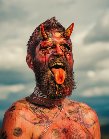 Halloween hell, evil, horror, darkness concept. Satan with red blood and wounds on face. Devil head with bloody horns. Vampire or dragon with open mouth. Demon man with beard showing tongue.