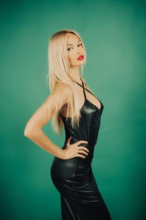 여자 검은 라텍스 드레스에서 포즈입니다. 녹색 배경에 긴 금발 머리를 가진 여자. 패션과 아름다움. 에로틱하고 유혹. 글 래 머 라이프 스타일 개념입