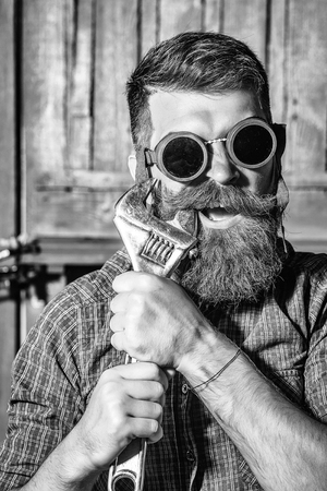 Bearded man hipster brutal male with beard and moustache in vintage biker sunglasses draws tooth with wrench on wooden background
