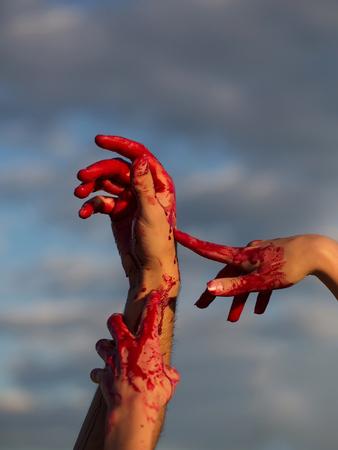 ゾンビの手が男性と女性の戦争の兵士の男と女の子または血の傷と青い空を背景には、皮膚上の赤い血の女性 写真素材 - 87989193