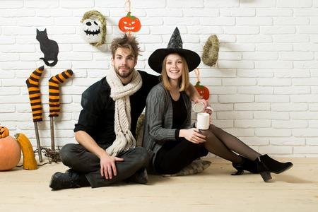 ハロウィーンの休日のお祝い概念。ウィッチ ハットで笑っている女の子。レンガの壁にはカップとの愛のカップル。身に着けているスカーフを男し