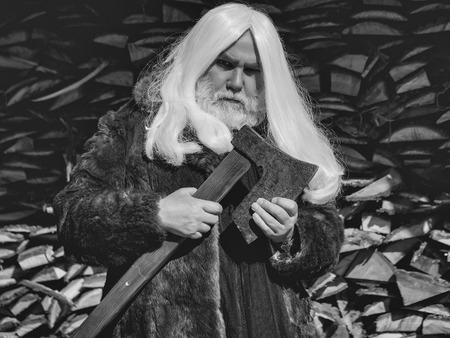 長い銀髪と毛皮のコートのひげを持つ老人ドルイドは、木製の背景に斧で立っています