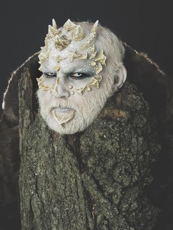 날카로운 가시와 사마귀가있는 괴물. 머리에 뿔 고블린입니다. 트리 정신 및 판타지 개념입니다. 검은 백그라운드에 오래 된 나무 껍질 뒤에 사제. 드 스톡 콘텐츠