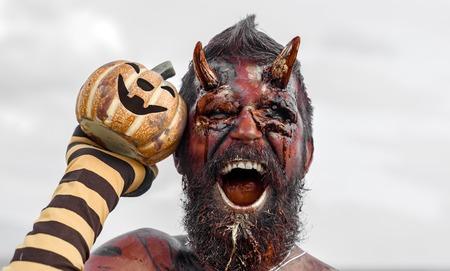 Halloween-satan met open mond, baard, rood bloed, wonden. De holdingspompoen van de duivelsmens in gestreepte sok. Draak met hefboom o lantaarn. Demon met bloedige hoorns op het hoofd. Kwaad, horror, hel concept. Stockfoto