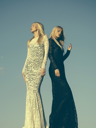 Choice, decision and future. Two girls with long blond hair posing on grey sky. Women wearing black and white dresses. Fashion and beauty. Opposites and contrasts concept. Stok Fotoğraf - 88769597