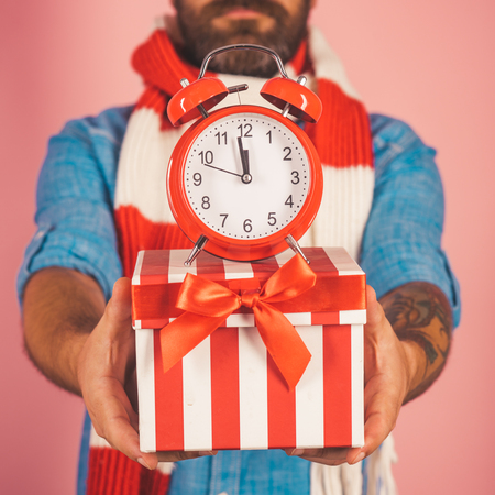 Christmas alarm clock on present box with red bow in male hands on pink background. Boxing day concept. Time to celebrate xmas, new year, winter holidays