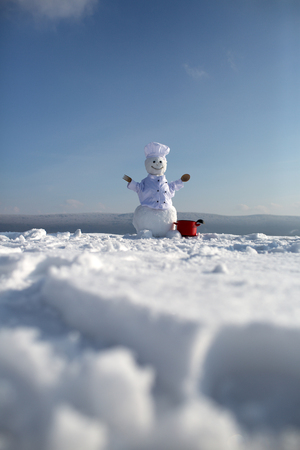 Christmas snowman in chef hat with red pot, wooden spoon and fork at blue sky in winter