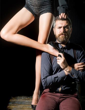 Romantiek en verliefd. Benen van vrouw in schoenen bij de mens met baard. Mens in overhemd op zwarte achtergrond, matriarchie wordt geïsoleerd die. Liefde en relaties, domineren. Jongen aan tafel met vrouwelijke benen.