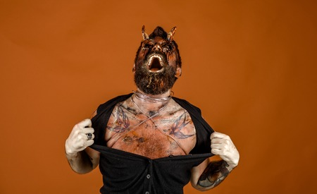 Halloween satan with red blood eyes, beard, wounds. Man devil rip shirt with anger on orange background. Aggression, evil, horror concept. Demon with bloody horns on head. Holiday celebration, cosplay Stock Photo