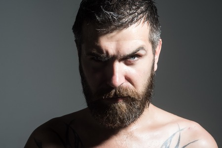 Man with long beard and mustache. Guy with naked shoulder on grey background. Barber fashion and tattoo beauty. Feeling and emotions. Hipster with serious face 版權商用圖片