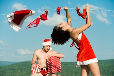 New year guy with muscular body on blue sky. Laundry and dry cleaning. Couple of happy man and girl hanging clothes for drying. Xmas red costume on rope with pin. Christmas man and woman family.