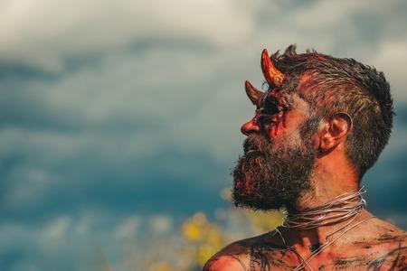 Halloween verleiding, hel, kwaad, horror, duisternis concept. Satan met rood bloed en wonden op de gelaatshuid. Dragon creature op bewolkte hemel. Demon man met baard. Duivelskop met bloedige hoorns, kopieer ruimte