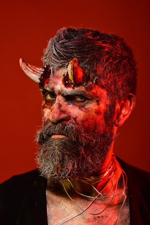 Halloween satan with beard, blood, wounds on face. Man devil on red background. Demon with bloody horns on head. Hell, death, evil, horror concept. Holiday celebration, cosplay.