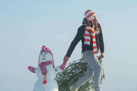 Hipster het slepen Kerstmisboom op de winterdag. Mens en sneeuwman die op blauwe hemel lopen. Kerel en sneeuwbeeld die hoeden en sjaals dragen. Kerstmis en Nieuwjaar. Vakantie feest concept. Stockfoto