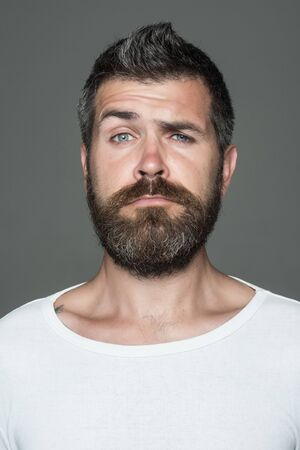 Hipster with serious face. Man with long beard and mustache. Barber fashion and beauty. Feeling and emotions. Guy or bearded man on grey background. 版權商用圖片